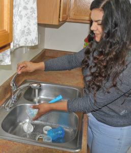 Cristal Aguirre Anchondo uses hot water to wash up a bottle for her infant son Jonathan. The single mother has a working hot water system in her Rifle home after three months of making do. Photo by Kelley Cox