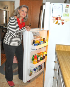 Trish O'Grady shows off the Energy Star refrigerator she received through the CARE program. It uses far less electricity than her old fridge. Photo by Kelley Cox