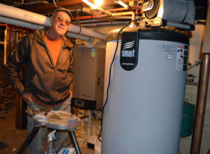 John Ackerman shows the new energy efficient boiler and hot water heater in the basement of the Pink Palace apartment house.