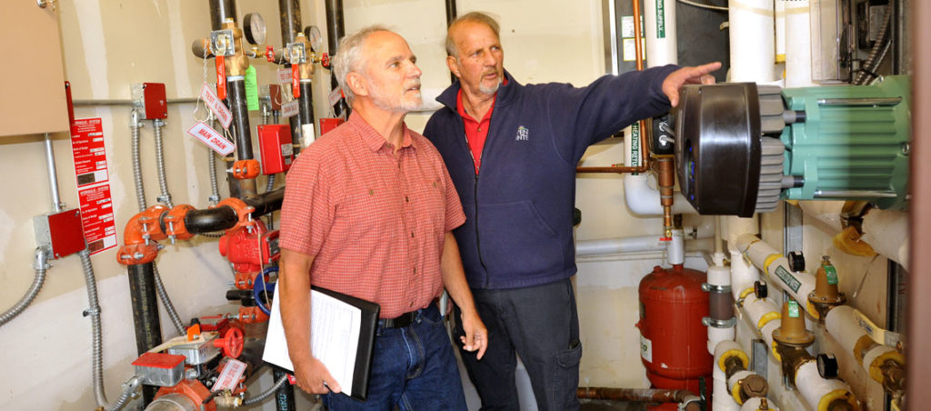 CLEER Energy Consultant Pete Waller, left, and Garfield County Facility Manager Frank Coberly in the mechanical room at the Garfield County Administration Building in Rifle. Photo by Kelley Cox.